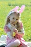 Девушка с ушами зайчика нося на траве весны зеленой Стоковые Фото