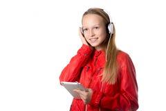 Девушка слушая к музыке на таблетке Стоковые Фото