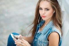 Девушка слушая к музыке, сидя на шагах Стоковые Изображения