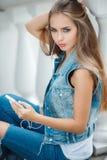 Девушка слушая к музыке, сидя на шагах Стоковое Изображение