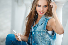 Девушка слушая к музыке, сидя на шагах Стоковые Фото