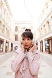 Девушка слушая к музыке с наушниками и смотря отсутствующий outdoors Стоковая Фотография