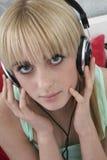 Девушка слушая к музыке через наушники Стоковое Изображение