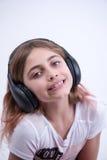 Девушка слушая к симпатичной музыке на наушниках Стоковая Фотография RF