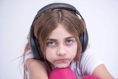 Девушка слушая к унылой музыке на наушниках Стоковое Изображение RF