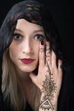 Девушка с хной на ее руке покрывая один глаз Стоковое Фото