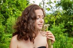 Девушка с цветками в ее руке в парке стоковое изображение