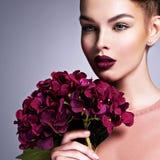 Девушка с цветками творческого стиля причесок пурпурными стоковая фотография rf