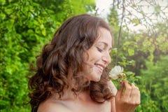 Девушка с цветком белой розы в ее руке в парке Стоковые Изображения