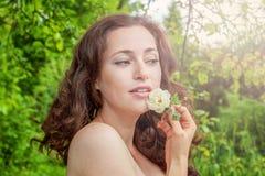 Девушка с цветком белой розы в ее руке в парке Стоковая Фотография RF