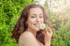 Девушка с цветком белой розы в ее руке в парке Стоковая Фотография