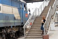 Девушка с чемоданом стоит около пассажирского поезда Стоковое Фото