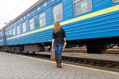 Девушка с чемоданом стоит около пассажирского поезда Стоковое Изображение RF