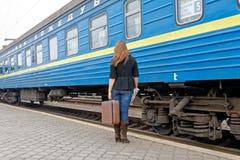 Девушка с чемоданом стоит около пассажирского поезда Стоковые Фотографии RF