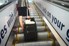 Девушка с чемоданом на эскалаторе Стоковая Фотография