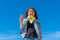 Девушка с черными длинными волосами против ясный смотреть голубого неба усмехаясь к камере показывая пальцы делая знак победы стоковое фото rf
