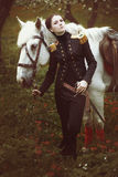 Девушка с шпагой от сказа стоит рядом с белой лошадью Стоковое Фото