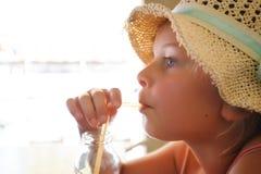 Девушка с шляпой выпивая с соломой стоковое изображение rf