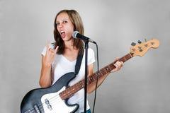 Девушка с электрической басовой гитарой на сером цвете стоковая фотография