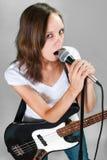 Девушка с электрической басовой гитарой на сером цвете стоковое фото
