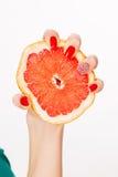 Рука с красным грейпфрутом обжатий ногтей Стоковые Фотографии RF