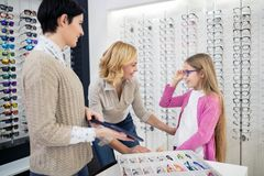 Девушка с eyeglasses смотря в зеркале стоковые изображения