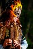 Девушка с shamanic маской пера и историческое платье в окрестностях полесья играя деревянную орнаментальную каннелюру стоковые фото