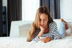 Девушка с smartphone на софе Стоковая Фотография