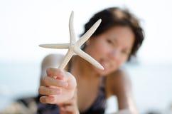 Девушка с starfish на пляже стоковое изображение rf