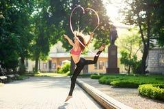 Девушка танцев делая пируэты с лентой в парке города Стоковая Фотография