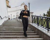 Девушка танцора наслаждаясь музыкой используя мобильный телефон Стоковое Изображение RF