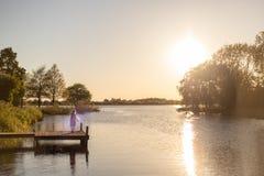 Девушка танцует на доке шлюпки на озере в заходе солнца стоковая фотография
