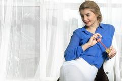 Девушка точит карандаши сидя в стуле стоковая фотография