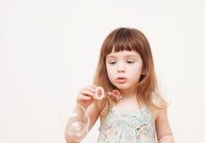 Девушка дует пузыри мыла на monophonic предпосылке Стоковые Изображения RF