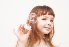 Девушка дует пузыри мыла на monophonic предпосылке Стоковые Изображения