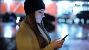 Девушка указывая палец на smartphone экрана на свете цвета bokeh освещенности фона в ноче атмосферической акции видеоматериалы