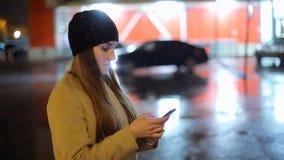 Девушка указывая палец на smartphone экрана на свете цвета bokeh освещенности фона в городе ночи атмосферическом сток-видео