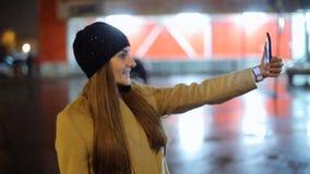 Девушка указывая палец на smartphone экрана на свете цвета bokeh освещенности фона в городе ночи атмосферическом акции видеоматериалы