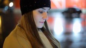 Девушка указывая палец на smartphone экрана на свете цвета bokeh освещенности фона в городе ночи атмосферическом видеоматериал