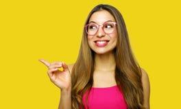 Девушка указывая показ на желтой предпосылке смотря на сторону Очень свежий и энергичный красивый усмехаться молодой женщины счас стоковые изображения rf