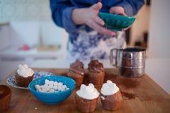 Девушка украшает пирожные, держа плиту, булочки и плиту ингридиентов для украшения на таблице Стоковая Фотография