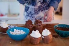 Девушка украшает пирожные, держа плиту, булочки Стоковые Фото