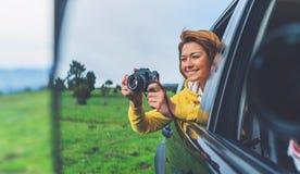 Девушка улыбки туристская в открытом окне автоматического автомобиля принимая фотографию нажимает на ретро винтажной камере фото, стоковые изображения