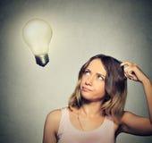 Девушка думает смотреть вверх на яркой электрической лампочке Стоковое Изображение