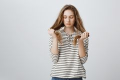 Девушка уныла ее плохих стренг волос Разделяя портрет хмурой докучанной молодой женщины держа волосы и быть осадкой, стоковое фото rf
