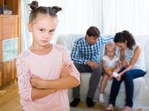 Девушка унылая из-за ревнивой более молодой сестры к родителям Стоковая Фотография