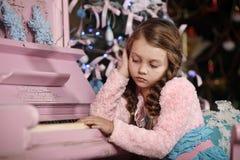 Девушка унылая о рояле Стоковое Изображение