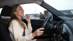 Девушка управляет автомобилем, она в хорошем настроении, она поет и танцует 4K медленный Mo сток-видео