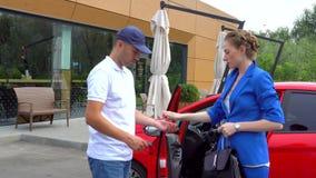 Девушка управляет автомобилем Она остановила и пришла из ее Гай приходит к красному автомобилю Она дает ему ключи и прогулку проч акции видеоматериалы