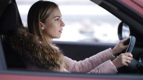 Девушка управляет автомобилем, стопами на пересечении, взглядами на дороге идет дальнейшее 4K медленный Mo акции видеоматериалы